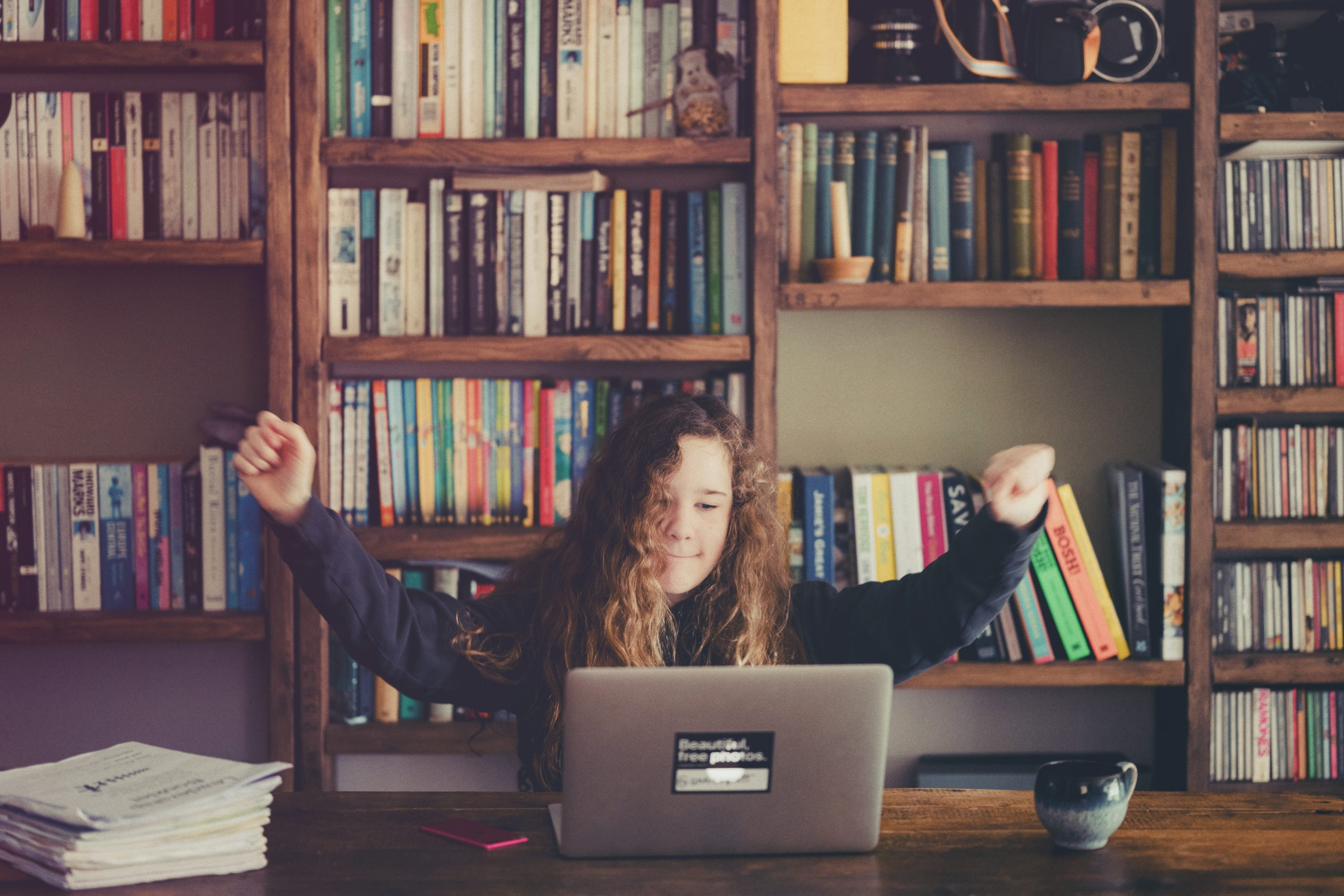 Enfant levant les bras de réussite devant son ordinateur